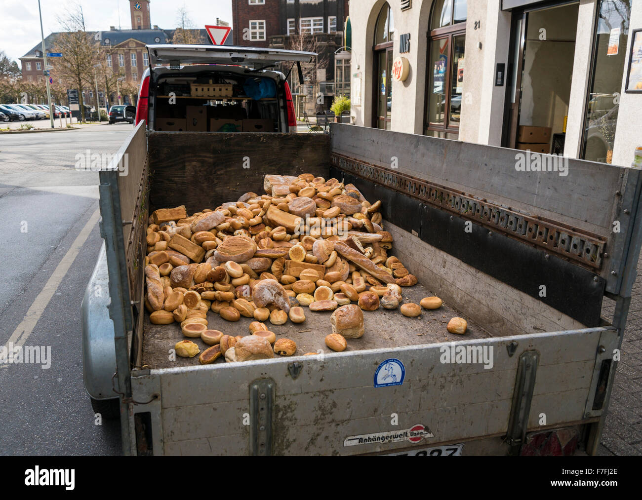 Loaves of bread and bread rolls from the previous day lie on a trailer in front of a bakery, waiting for disposal. - Stock Image