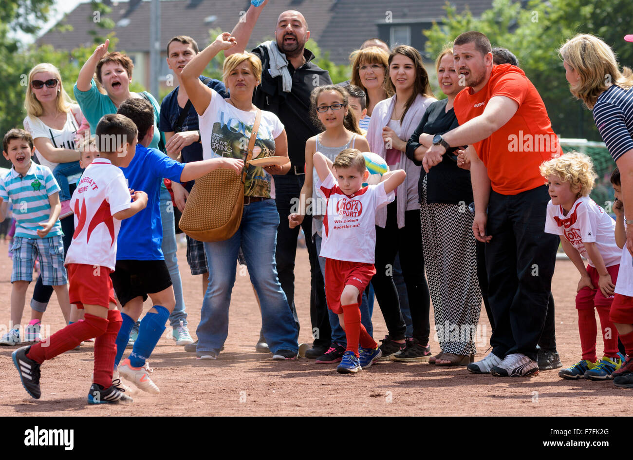 Parents of football / soccer playing children cheer for their children. - Stock Image