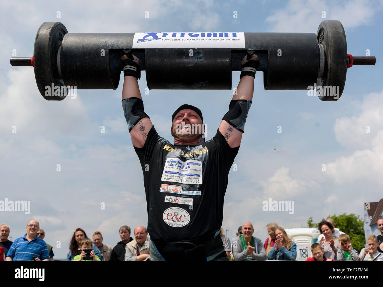 A strong man proves his strength at a public athletics sports event. - Stock Image