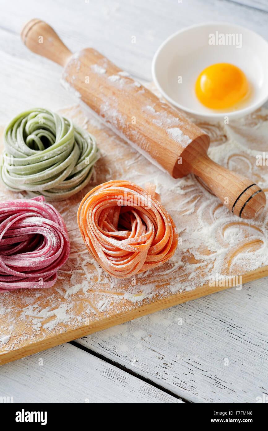 raw italian color pasta and rolling pin, food closeup - Stock Image