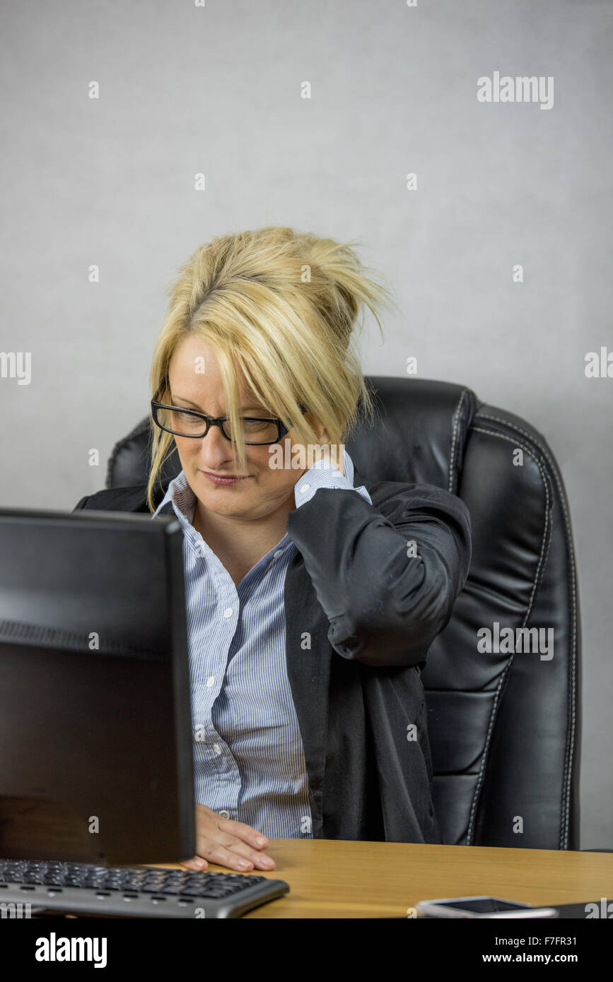 A Female office worker sitting at her desk on her 9 to 5 job - Stock Image