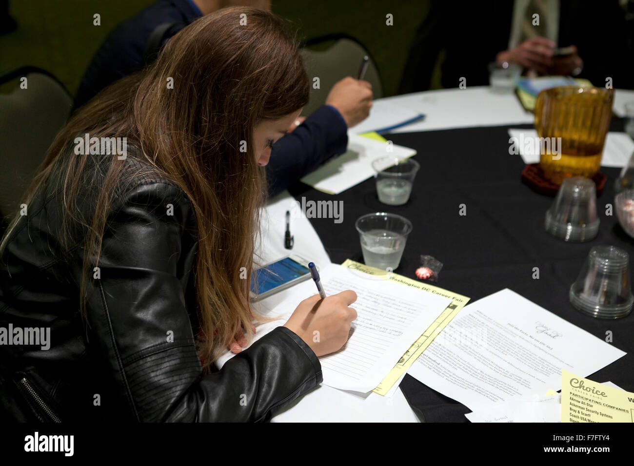 Young woman filling out an application at job recruiting fair - Arlington, Virginia USA - Stock Image