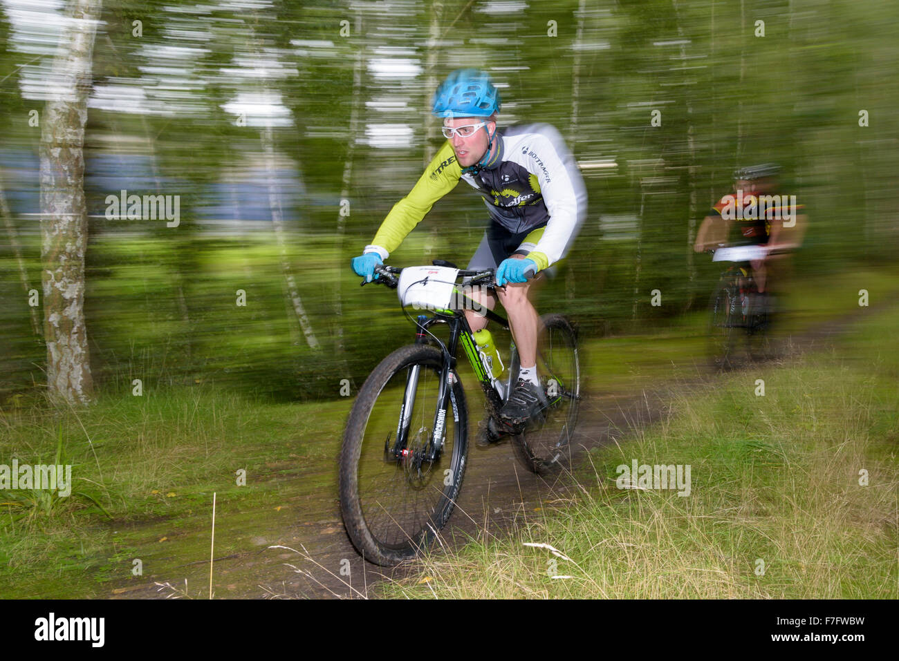 Two mountain bikers ride through a forest at a mountain biking competition - Stock Image