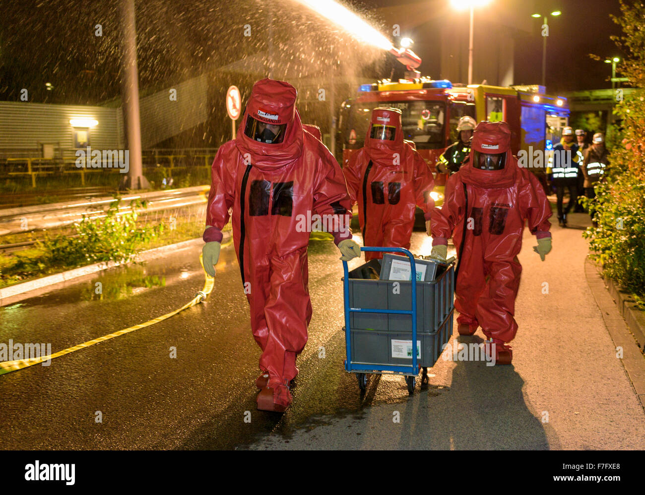 Firefighters in abc protective suits practice for an emergency in a power plant. - Stock Image