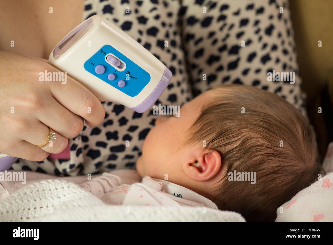 mum checking newborn baby temperature with infrared thermometer - Stock Image