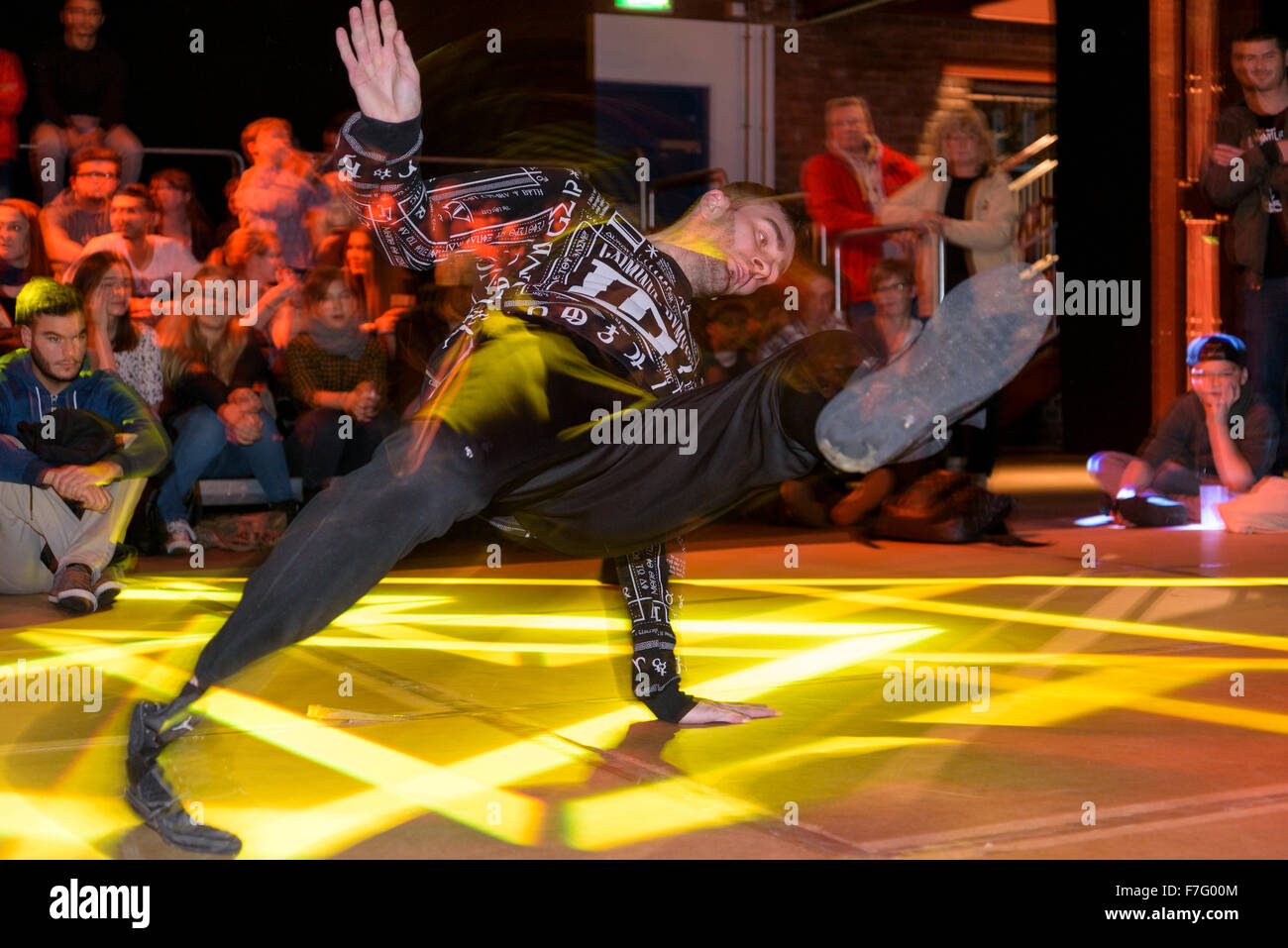 A young break dancer performs on a stage at a break dance competition. - Stock Image