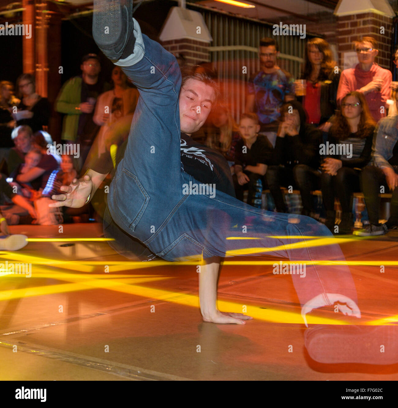 A young break dancer performs on a stage at a break dance competition. Stock Photo
