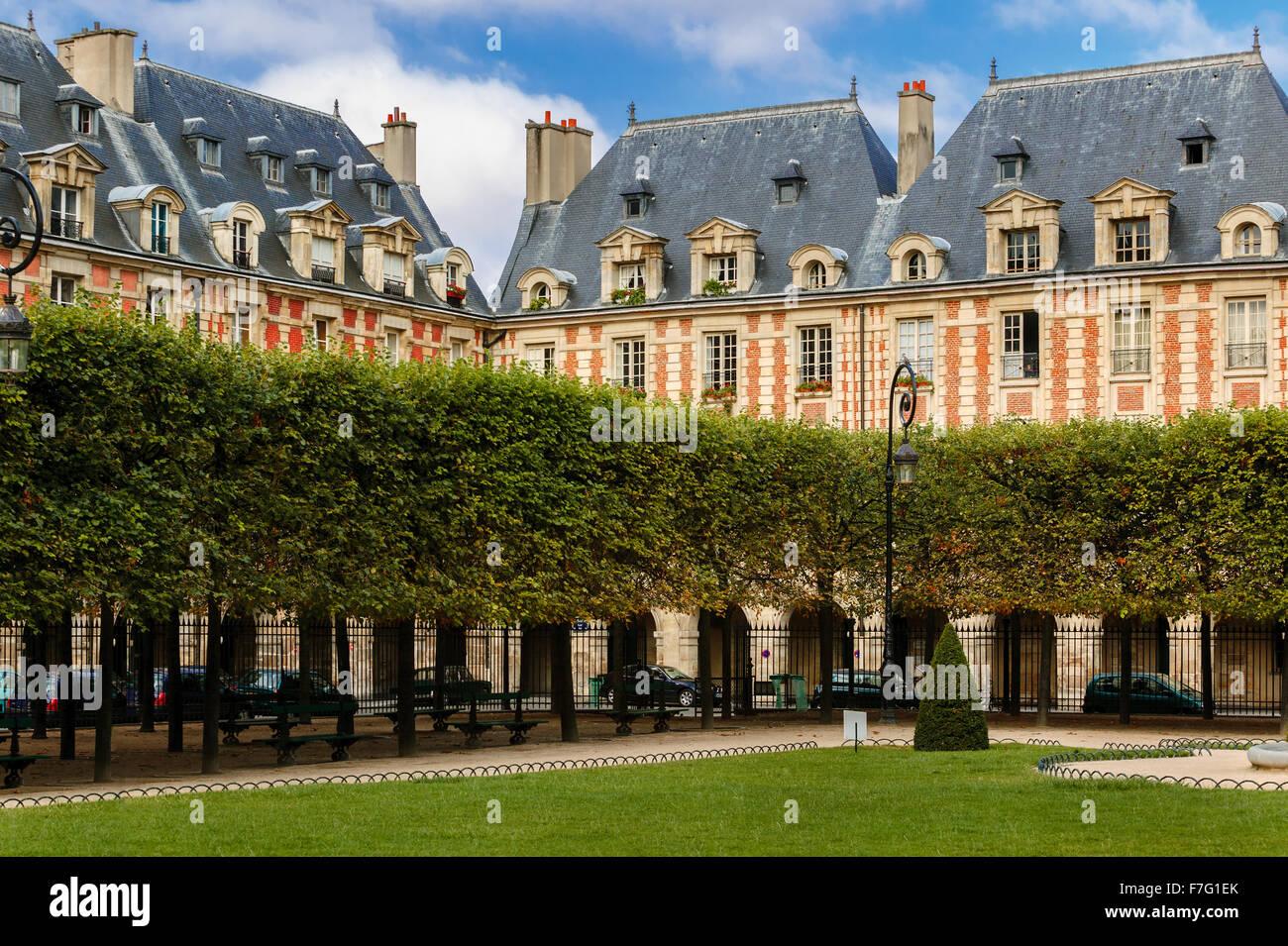 Garden and housefronts (with blue slates dormer roofs) on Place des Vosges in Le Marais, 4th arrondissment, Paris, - Stock Image