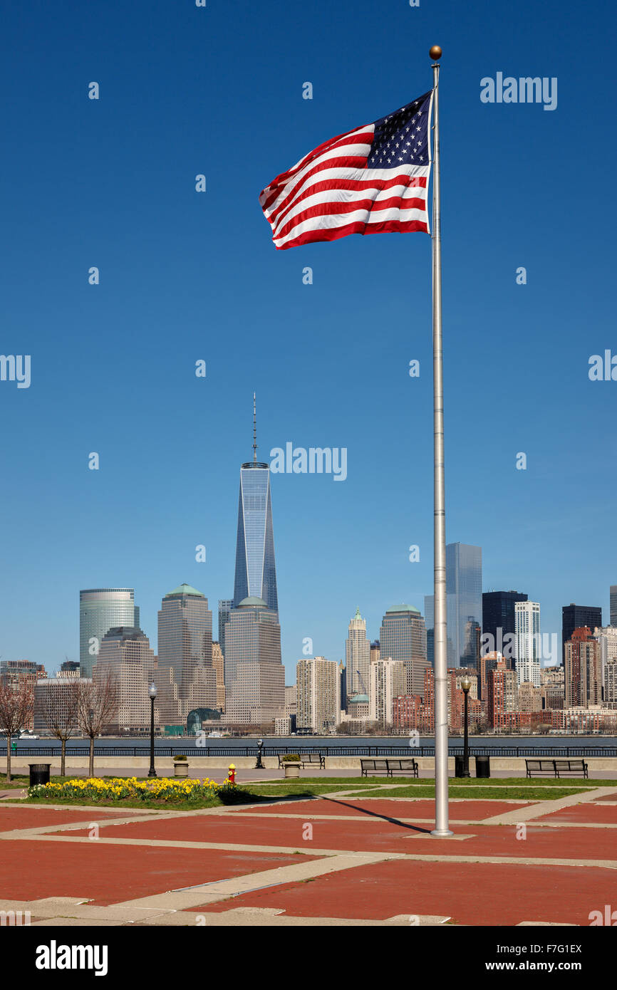 American flag standing tall in Liberty State Park, New Jersey, with a view of Lower Manhattan skyscrapers, New York - Stock Image
