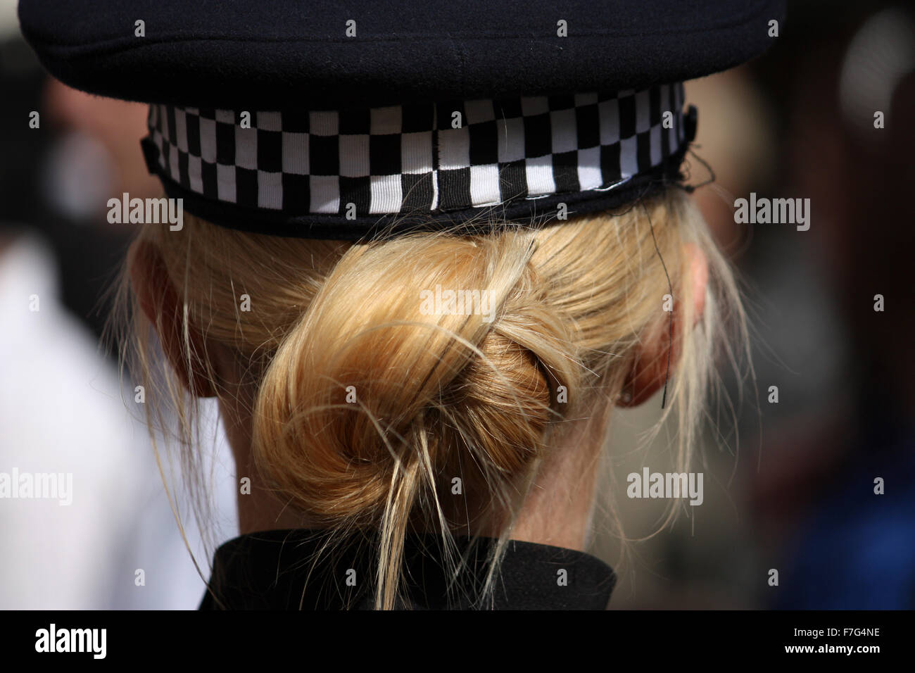 A rear photograph of a blonde Kent police woman and here hair tied up behind her and tucked into her police cap - Stock Image