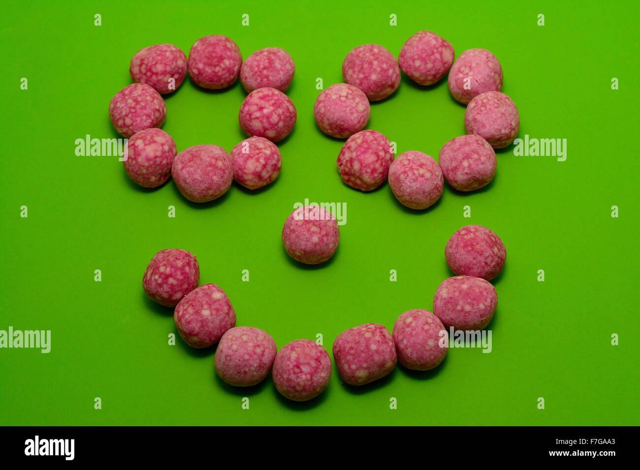 Smiling Face made with pink bonbon sweets - Stock Image