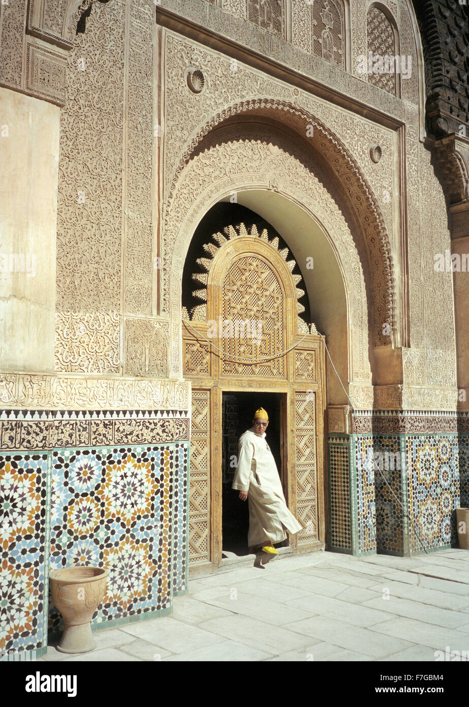 A Muslim Moroccan man steps into the courtyard at Ali ben Youssef Medersa inside the medina at Marrakech, Morocco, - Stock Image