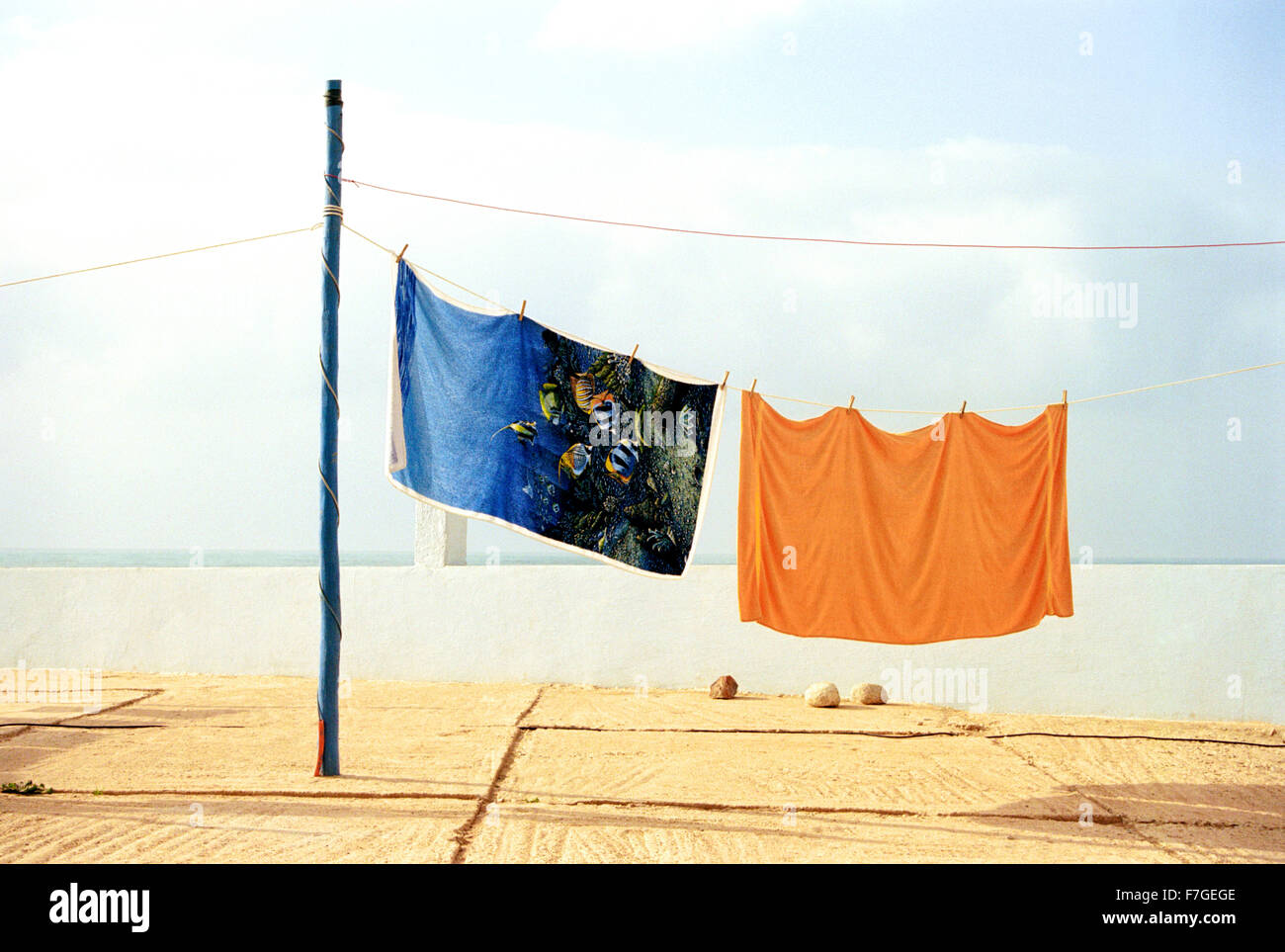 Colorful beach towels hand to dry at a camping ground in Sidi Ifni. Morocco - Stock Image