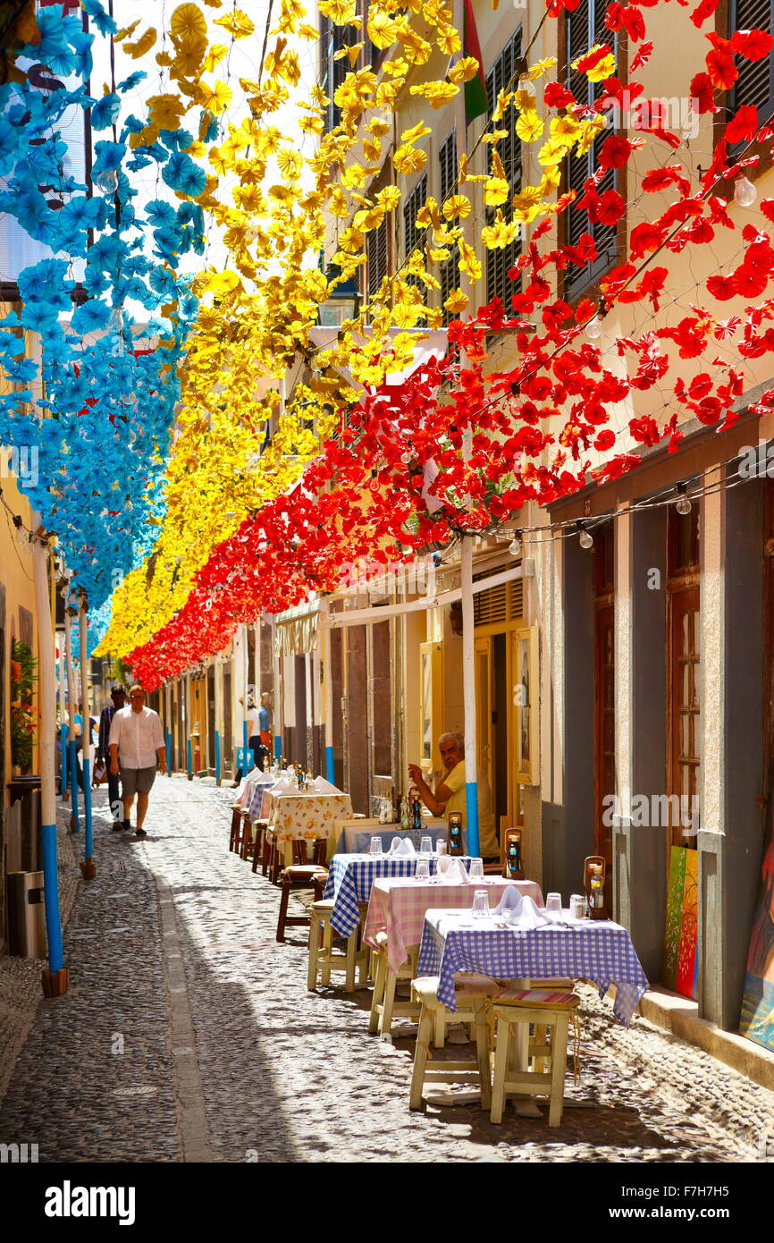 Street decorated with paper flowers on feast of Madeira, Funchal old town, Madeira Island, Portugal - Stock Image