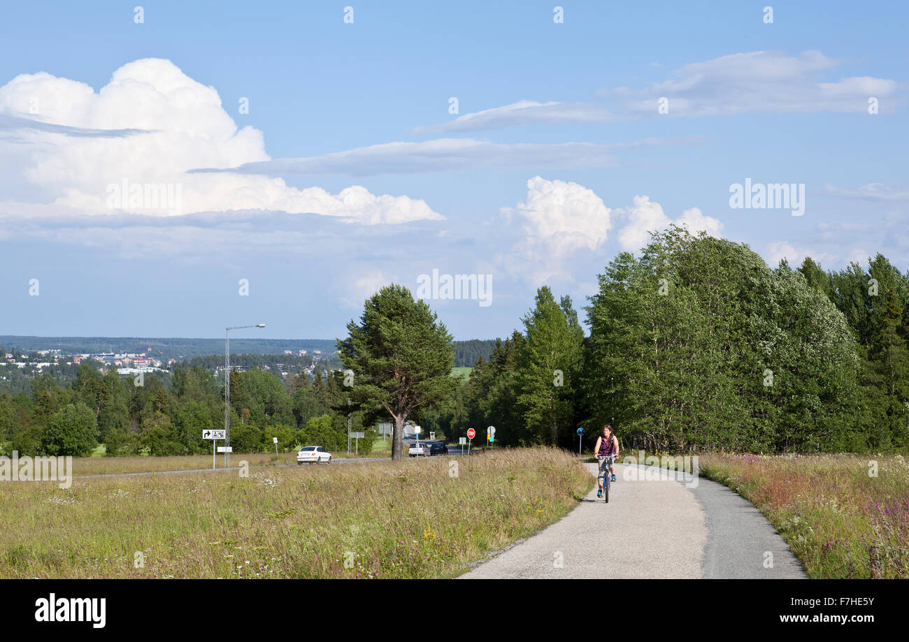 FROSON, SWEDEN ON AUGUST 07, 2015. Unidentified cyclist moves upwards the pathway. Sunshine and heavy showers. Editorial - Stock Image