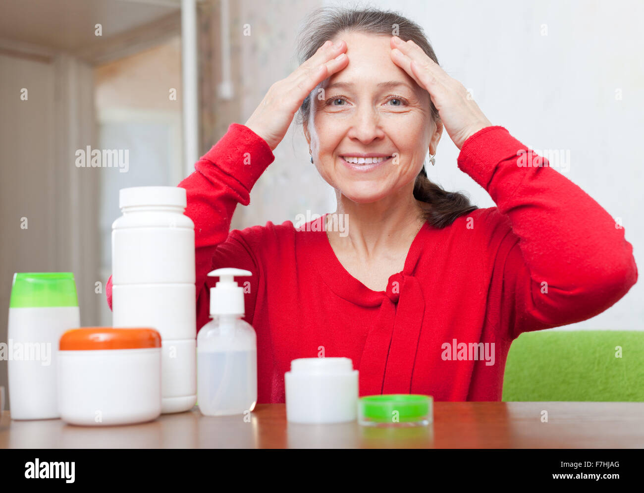 mature woman in red dress uses cosmetic cream in home interior