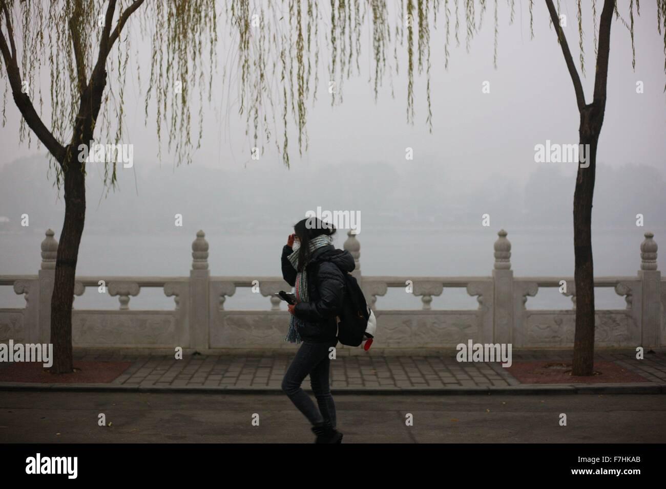 Beijing, China. 1st Dec, 2015. A girl wearing respirator walks at Shichahai in Beijing, capital of China, Dec. 1, - Stock Image