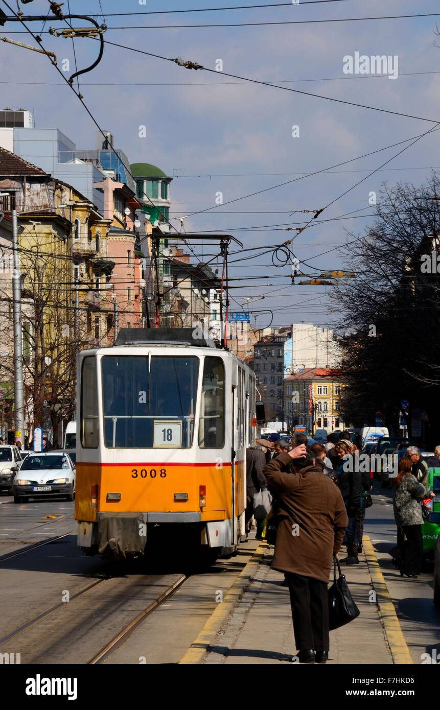 Yellow streetcar tram trolley with commuters in Central Sofia Bulgaria - Stock Image