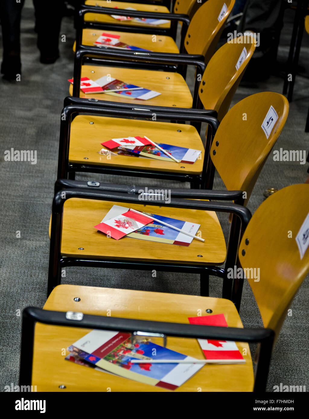 Row of chairs with Canadian flags and information for new Canadian citizens.  Assigned seating at the citizenship - Stock Image