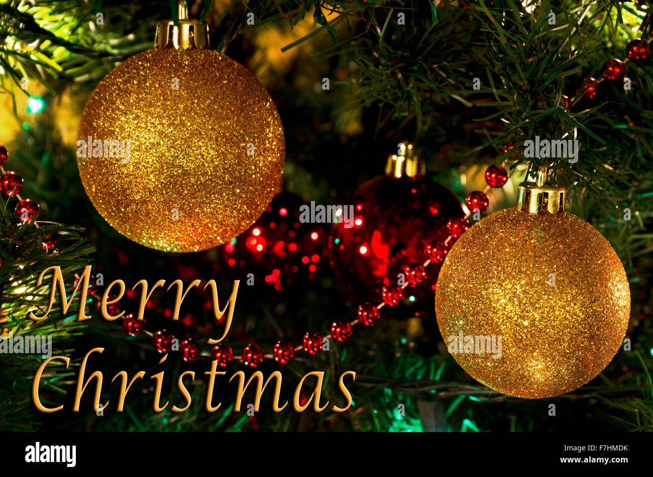 Sparkling Gold Ball Ornaments On A Christmas Tree With A Merry Stock