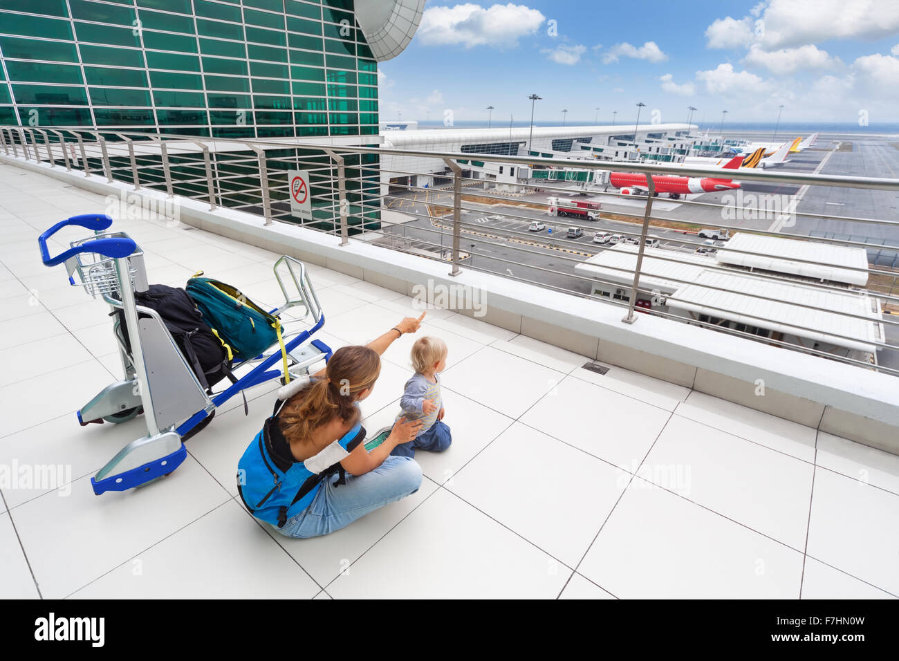 Young mother and little baby boy wait for boarding to flight in airport transit hall and looking at airplane near - Stock Image