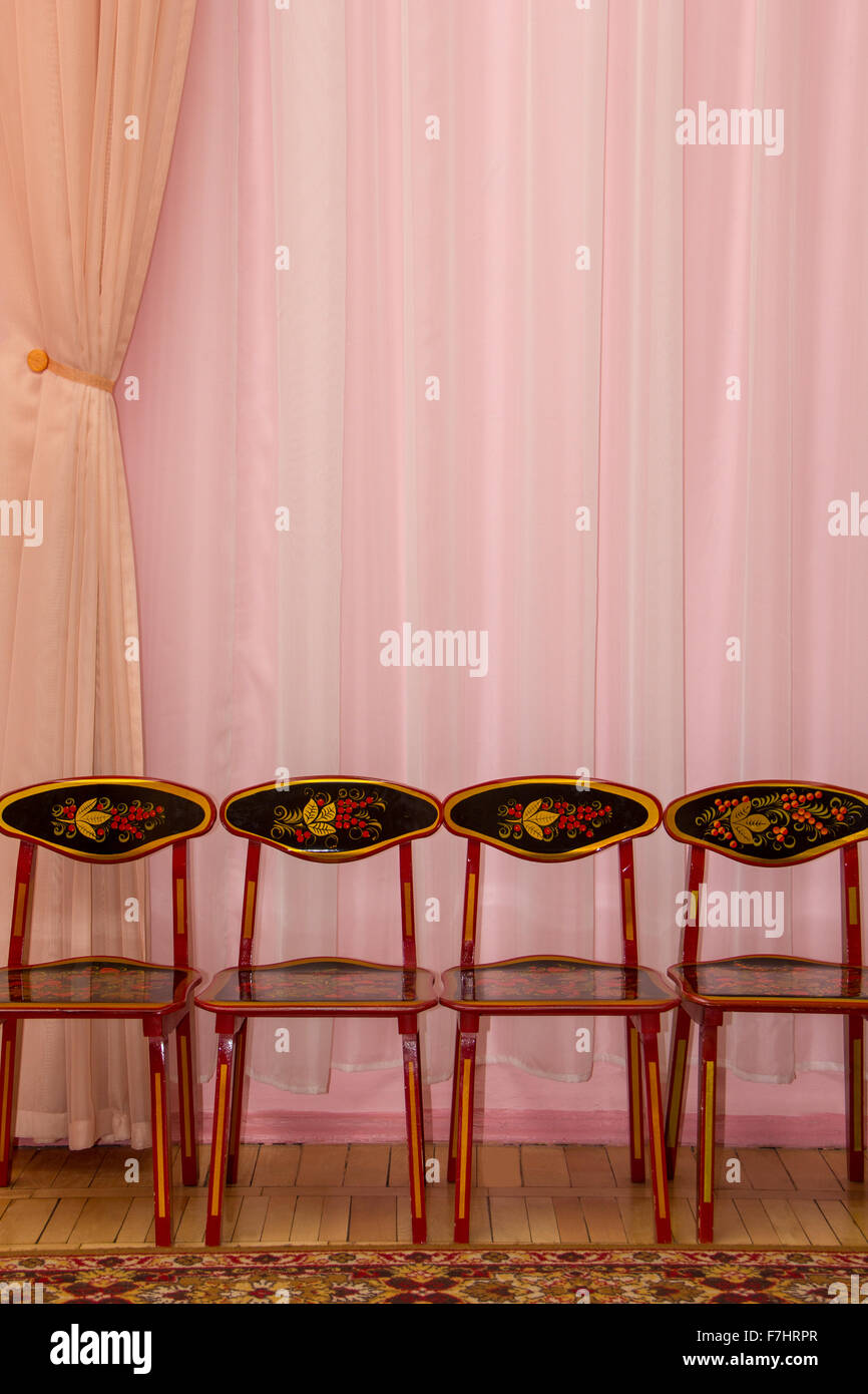 pink curtain background with four children chairs - Stock Image