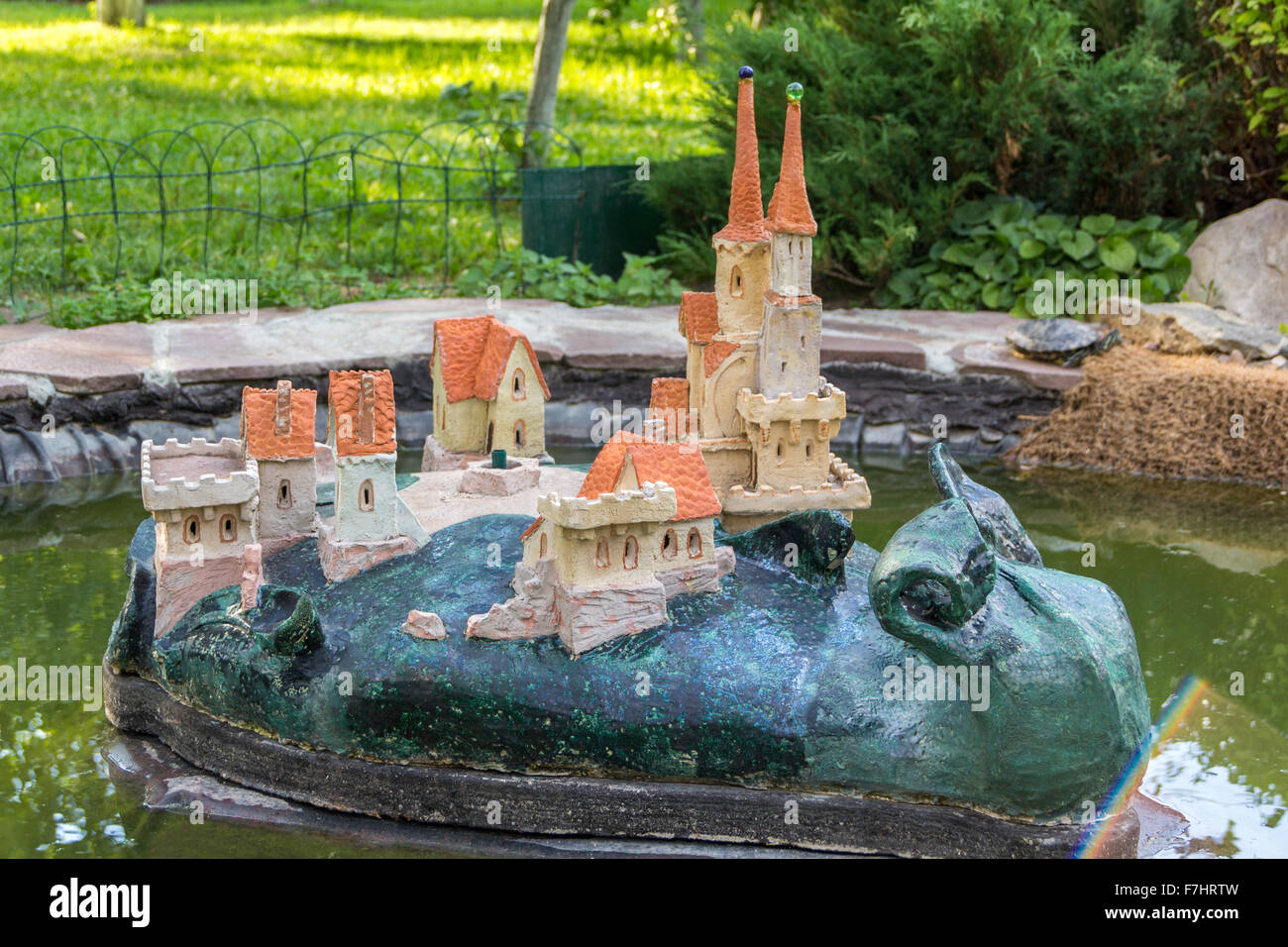garden statue of a snail with castle on its back in a pond - Stock Image