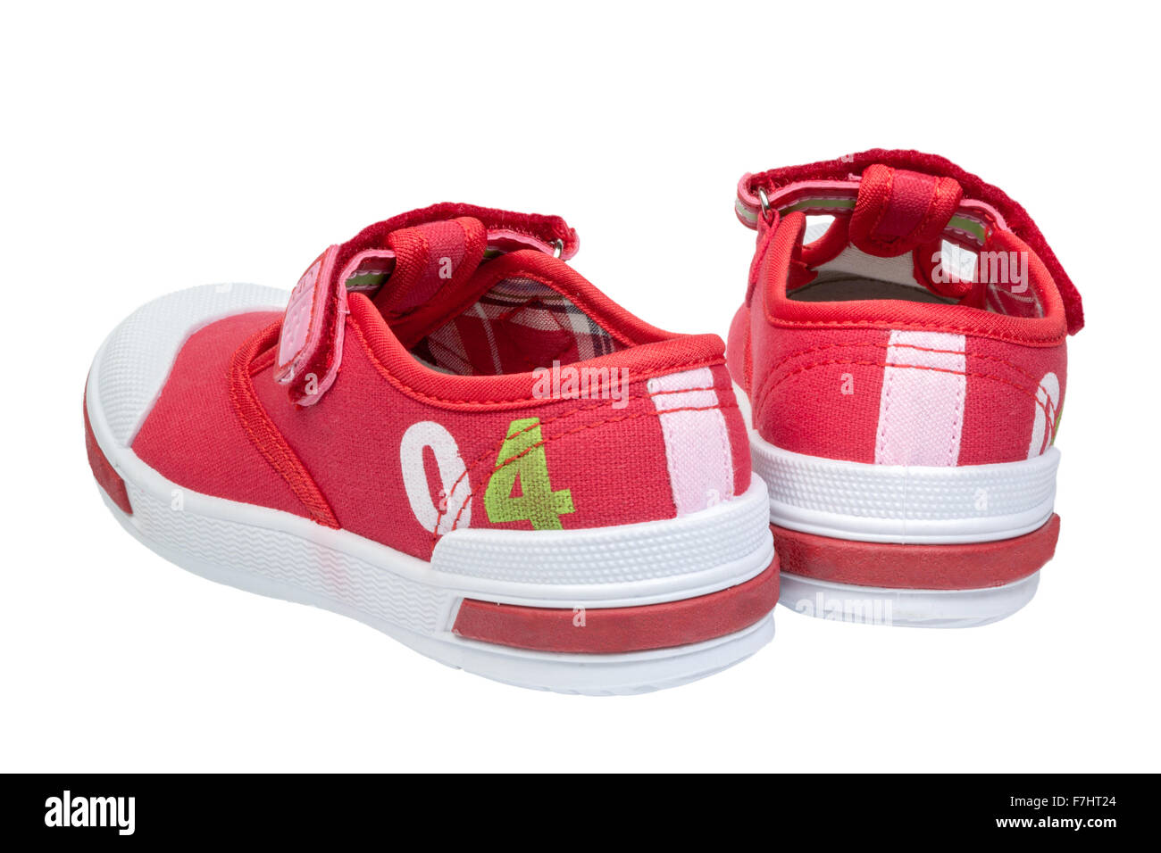 pair of red child  sneakers isolated on white background - Stock Image