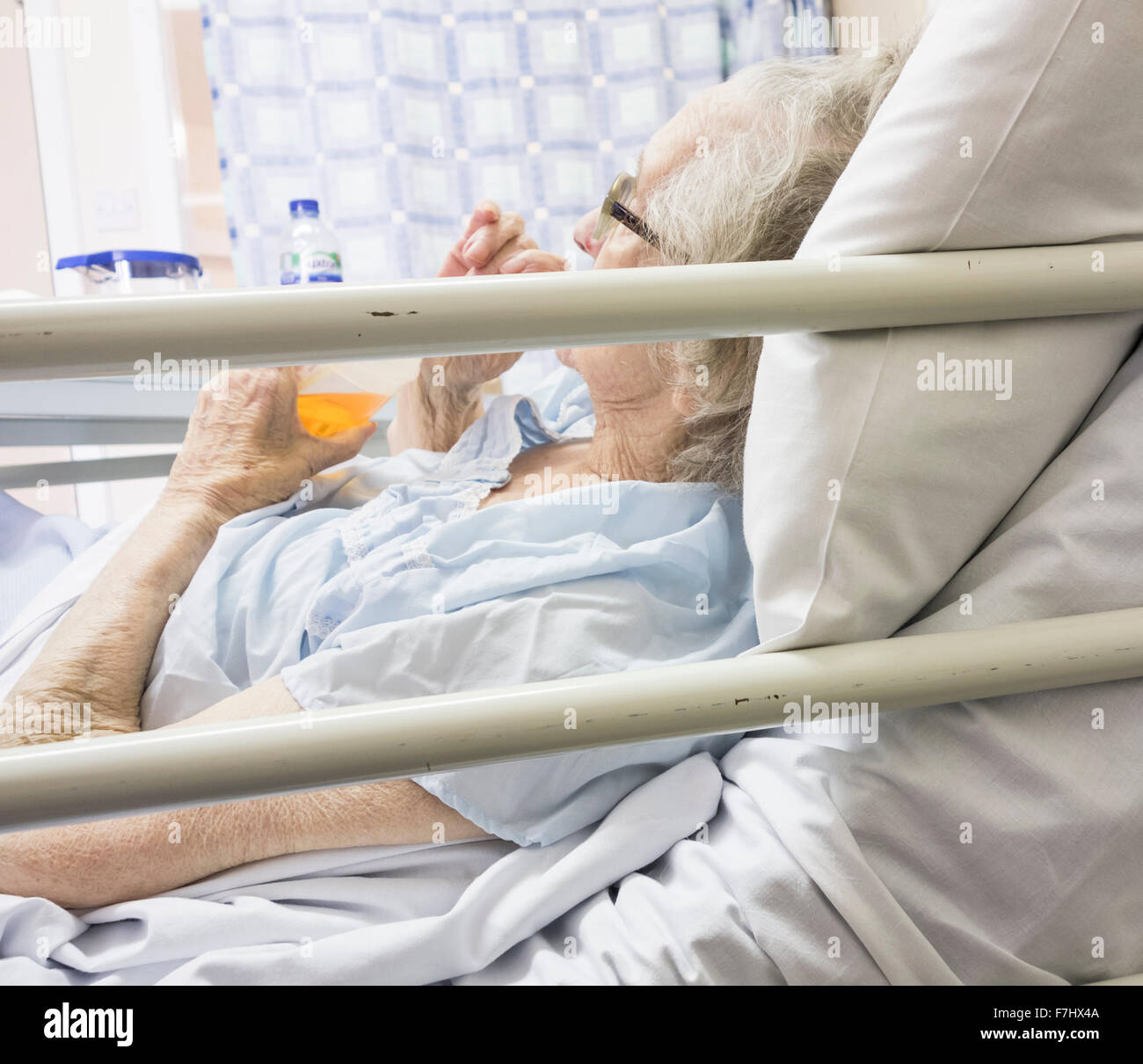 Ninety year old female patient drinking in bed in National Health Service Hospital in England, UK. - Stock Image