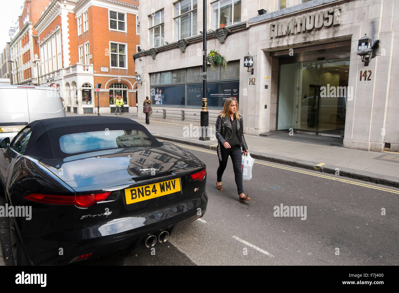 Jaguar F-Type car parked opposite Film House with poster for Spectre in the window in Wardour Street, Soho, London, - Stock Image