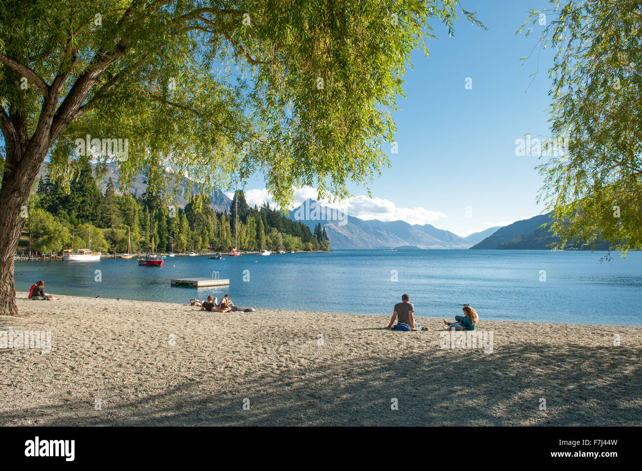 Tourists relax at the shore of Lake Wakatipu in Queenstown, New Zealand. - Stock Image