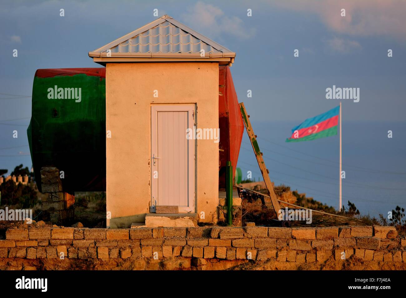 Azerbaijani flag in front of and matching colours from sky, hut and water tank - Stock Image