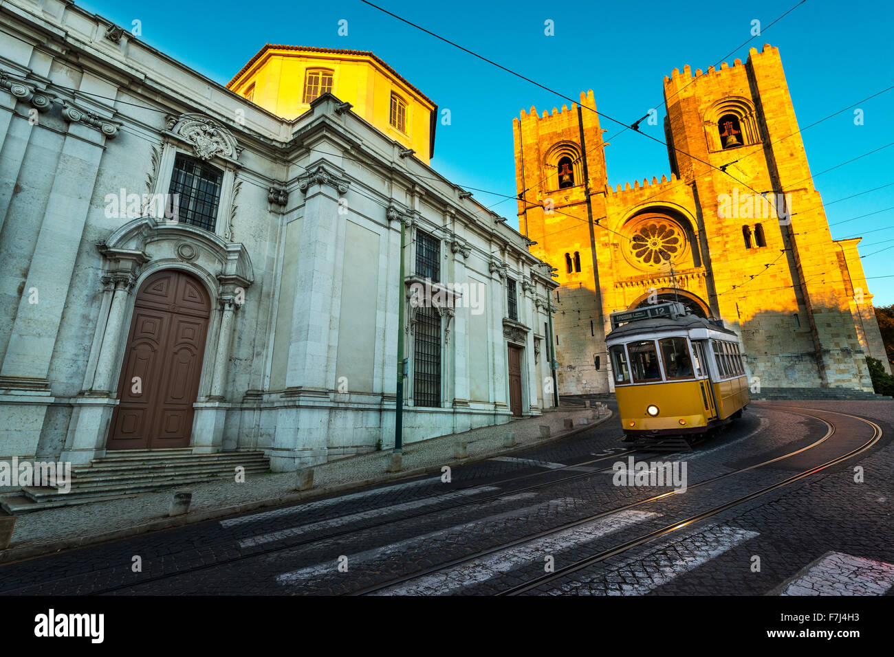 Tram in front of the Lisbon Cathedral at sunset - Stock Image