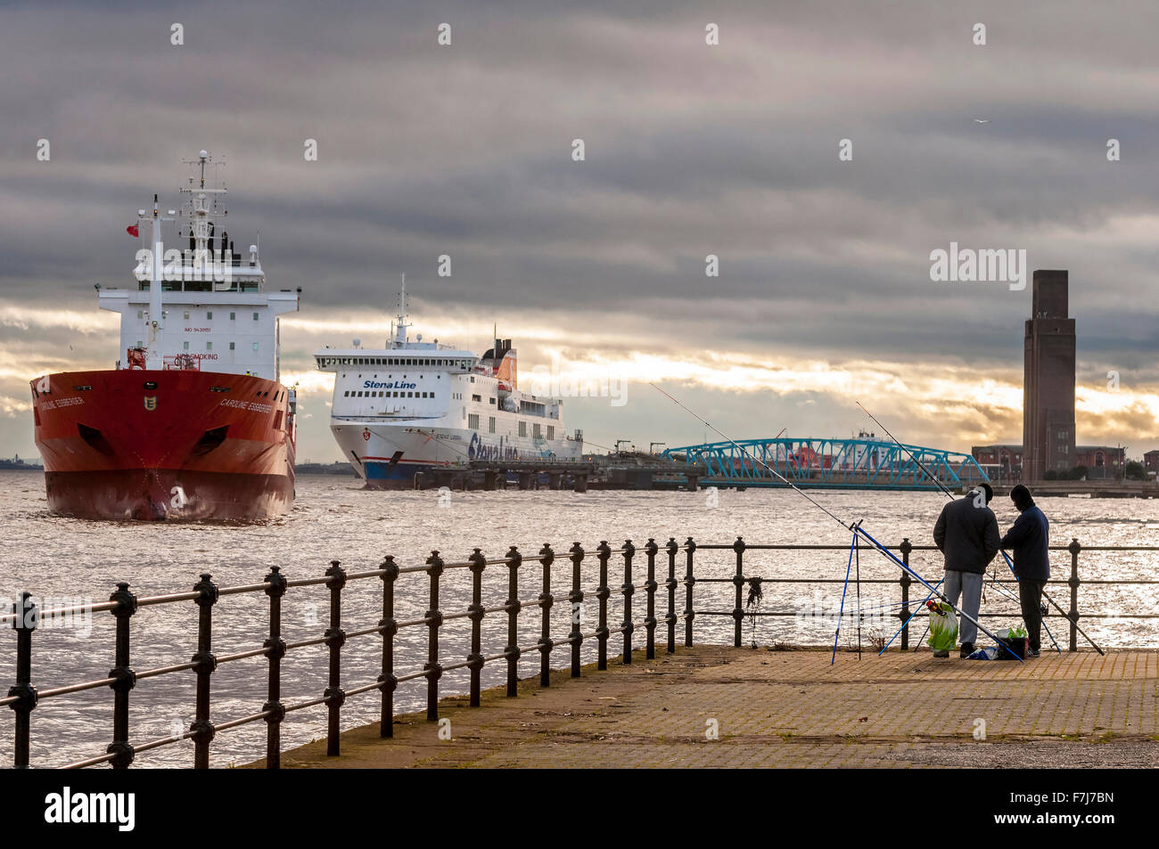 The oil and chemical tanker ship the Caroline Essberger from Holland in the river Mersey watched by two anglers - Stock Image