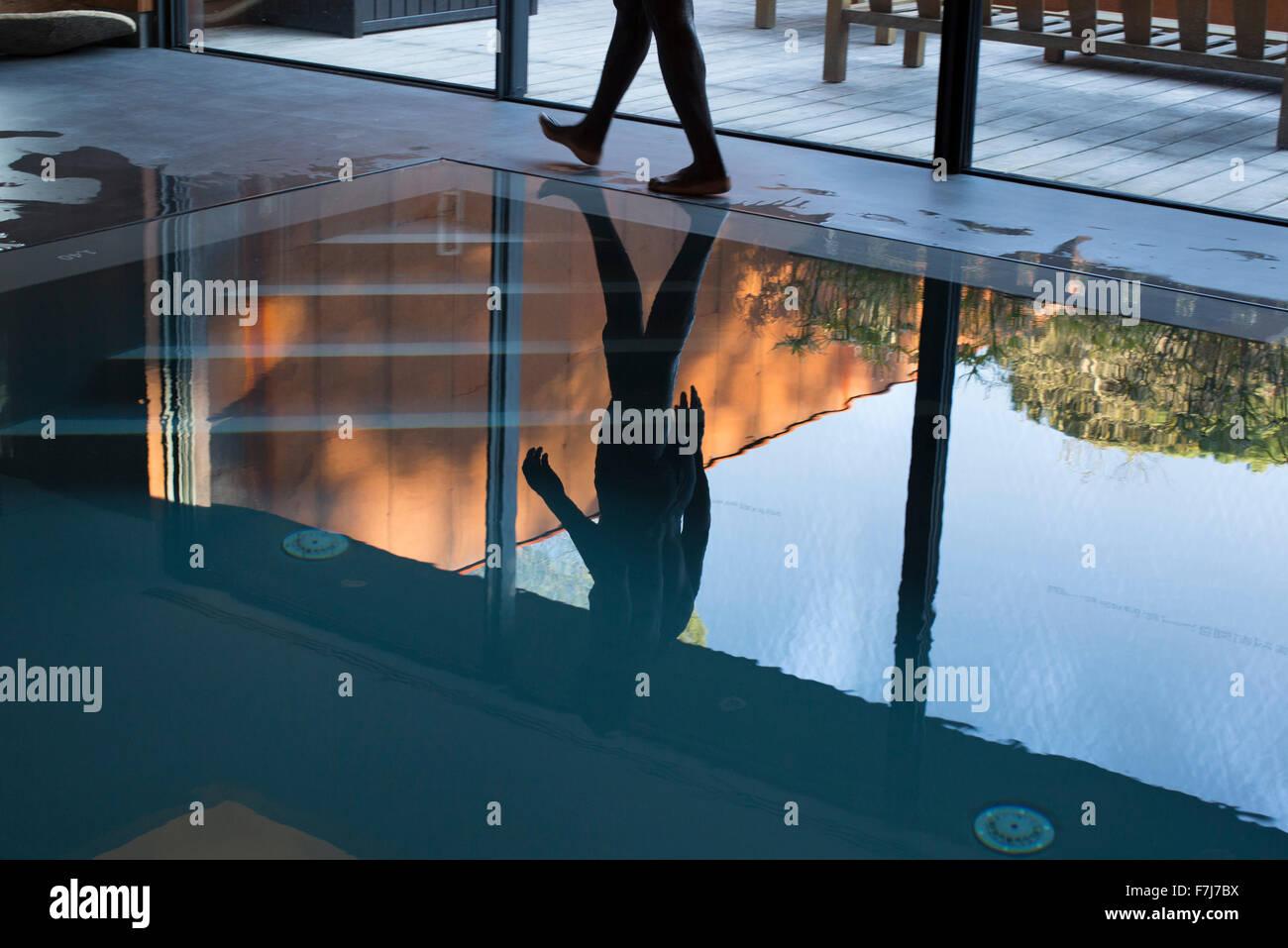 Man walking beside pool, reflected on water - Stock Image