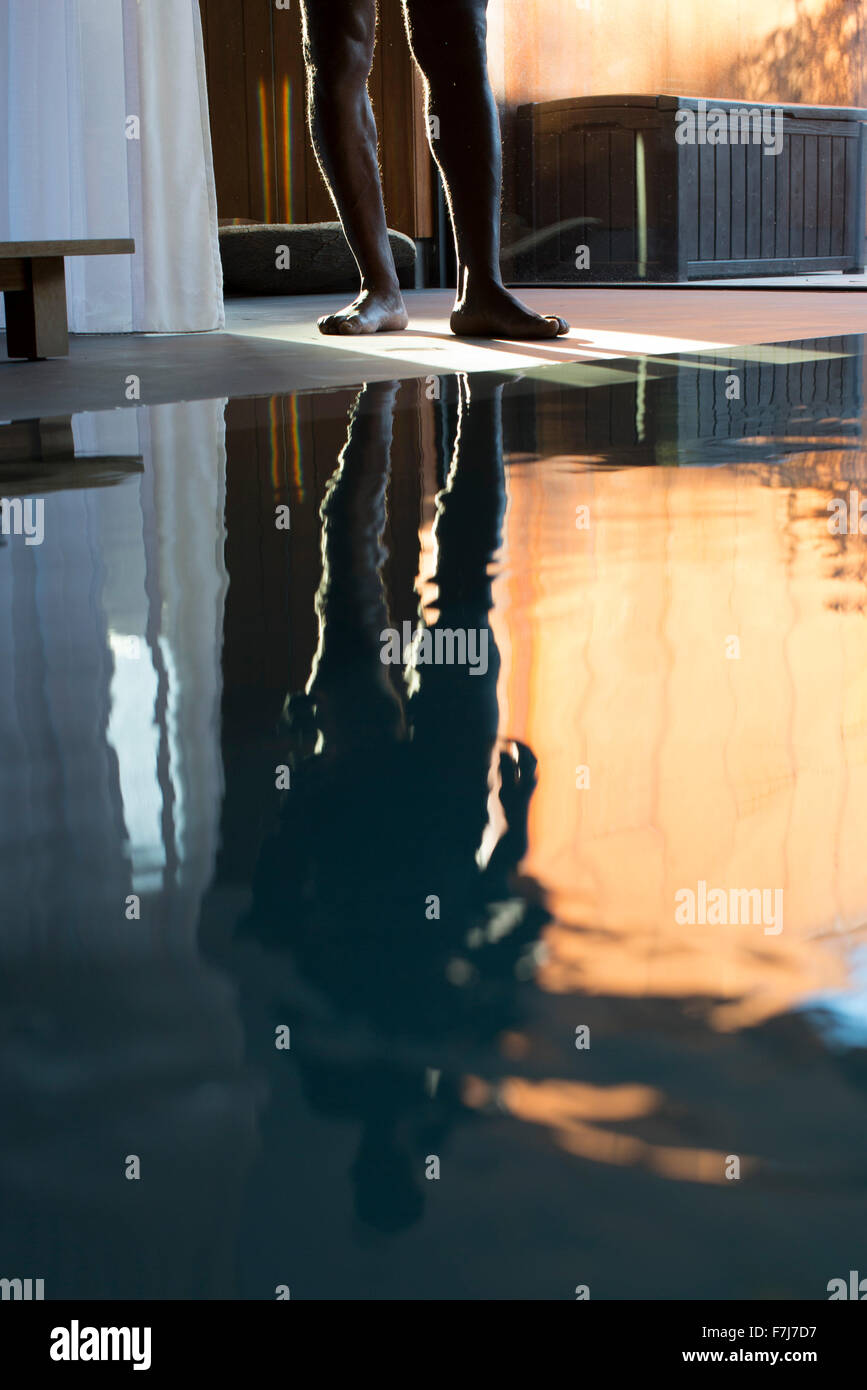 Man's reflection on spa swimming pool, low section Stock Photo