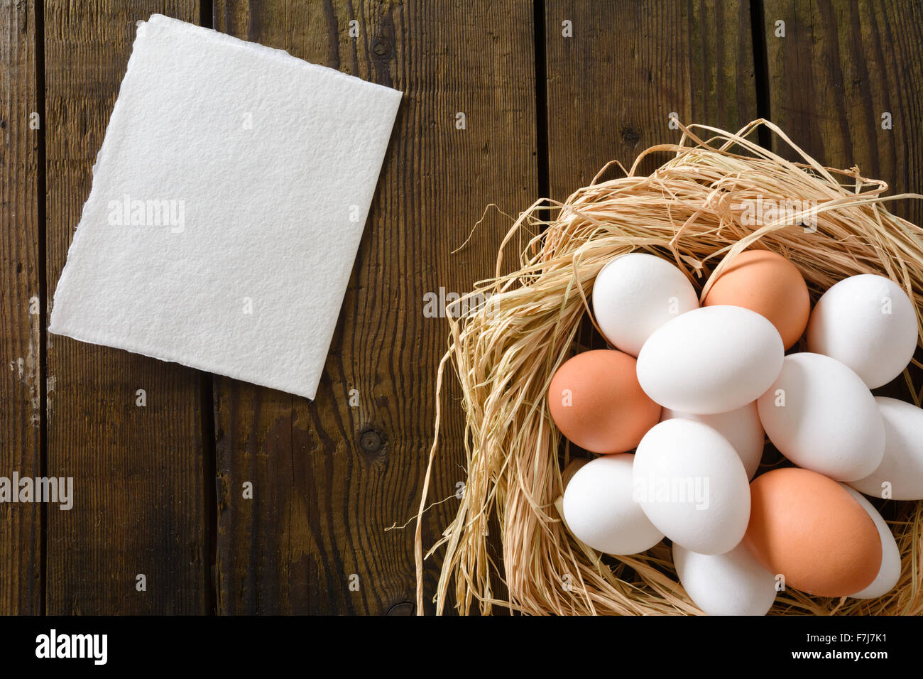 Eggs in the  strawy nest with  hand made paper card on the vintage wooden board - Stock Image