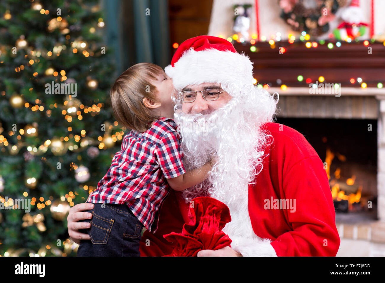 santa claus and little child boy kid telling his christmas wish in santa claus near the christmas opposite fireplace - Santa Claus Children