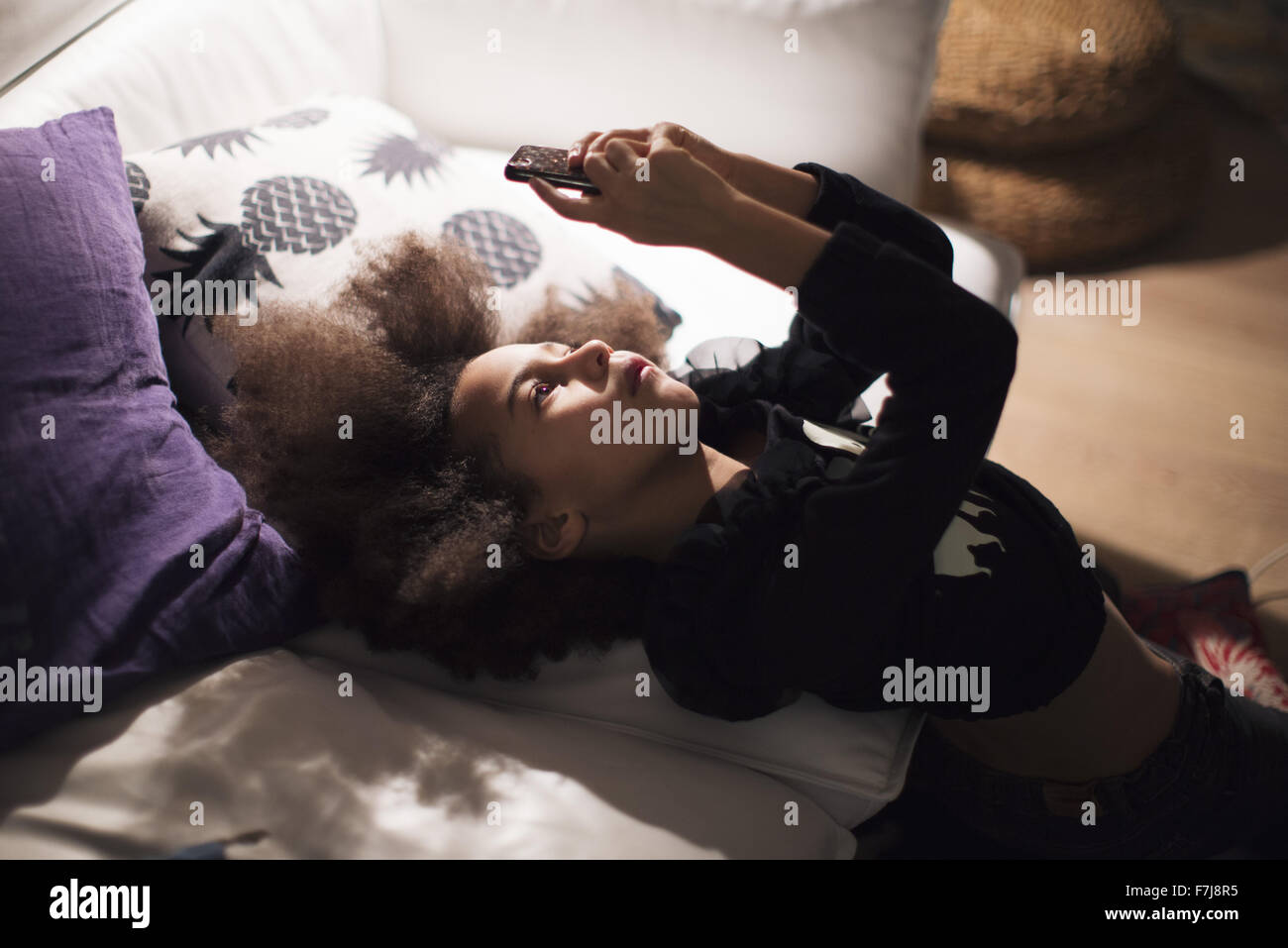 Girl reclining against sofa, engrossed in smartphone - Stock Image