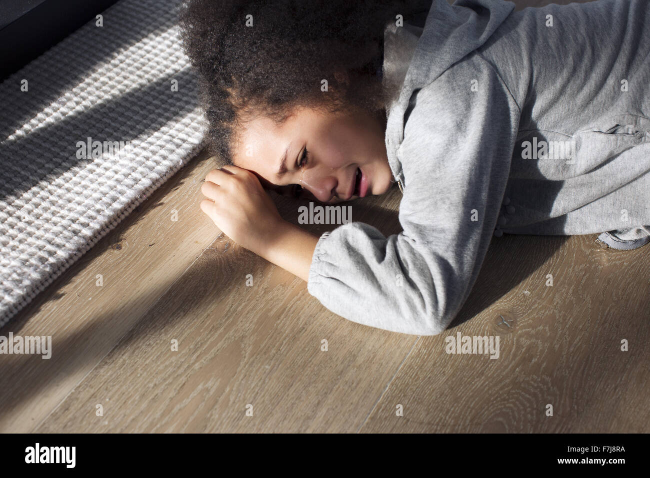 Girl lying on floor crying - Stock Image