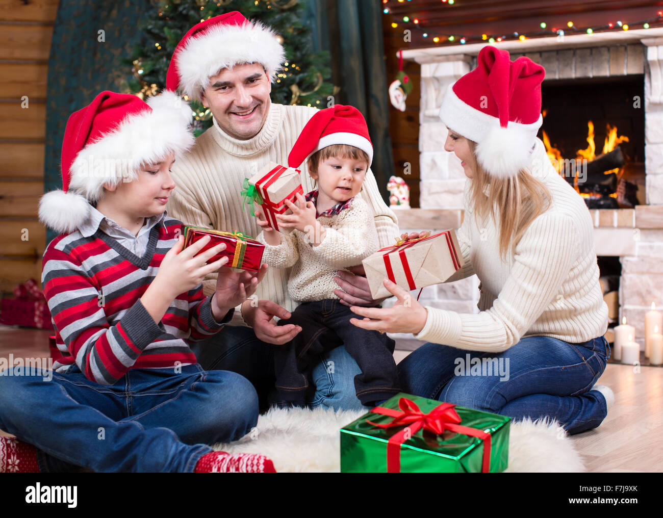 Family exchanging gifts in front of Christmas tree - Stock Image