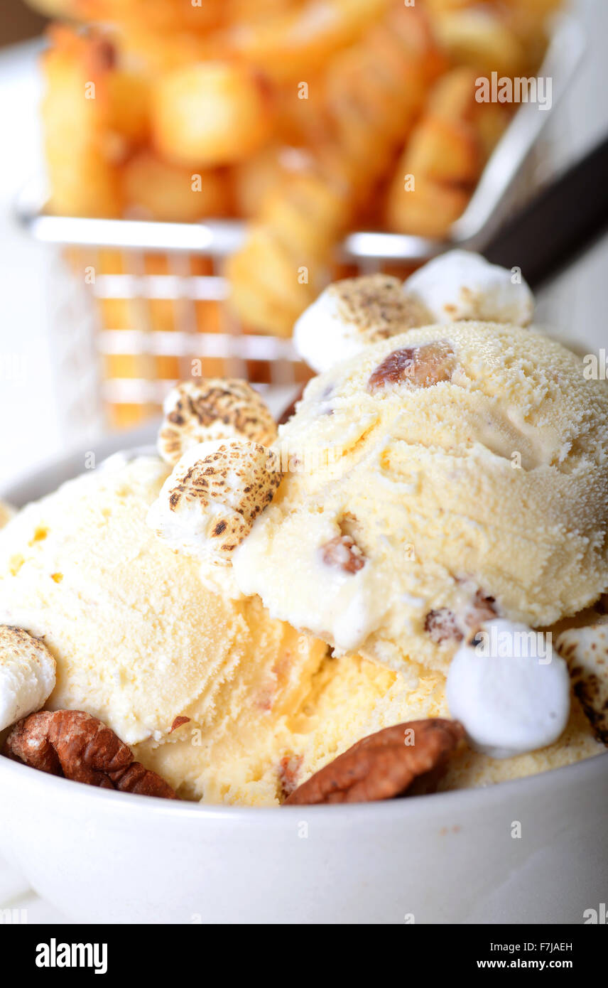 Bowl of Butter Pecan Ice Cream with whole pecans and toasted marshmallows with crispy French Fries - Stock Image