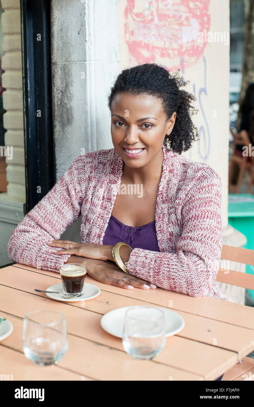 Woman sitting at sidewalk cafe - Stock Image
