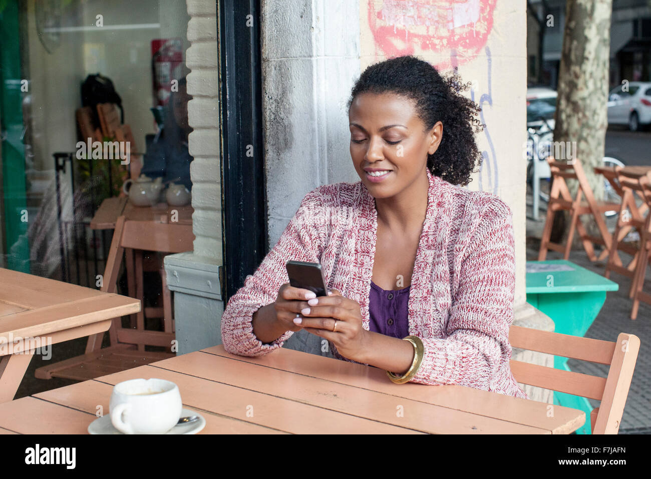 Woman using cell phone at sidewalk cafe - Stock Image