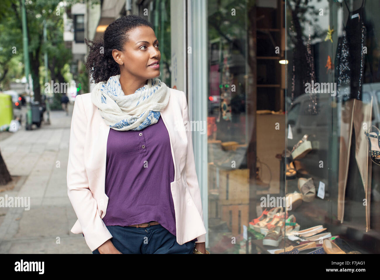 Woman looking at shop window - Stock Image
