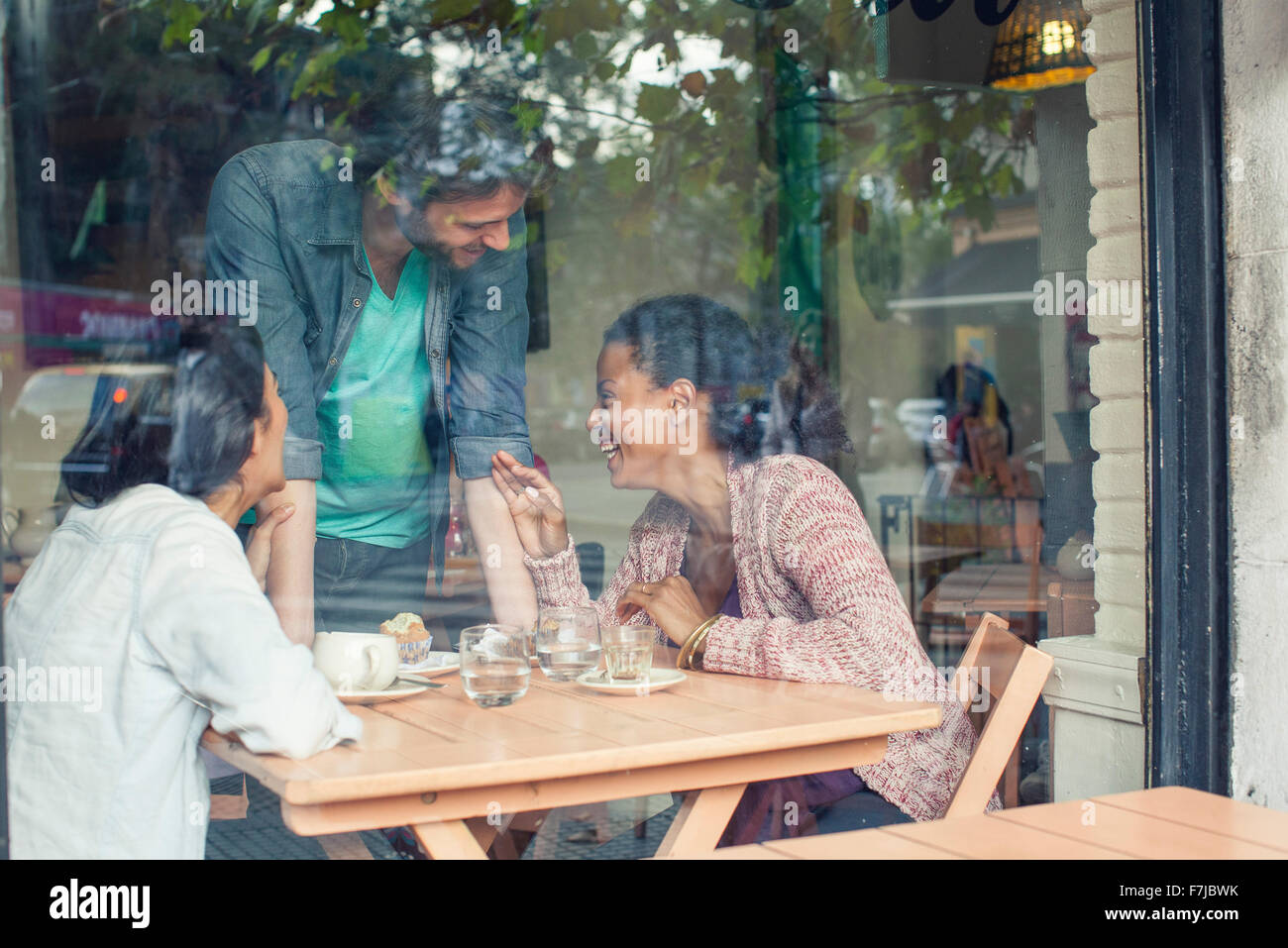 Waiter talking to customers in coffee shop - Stock Image