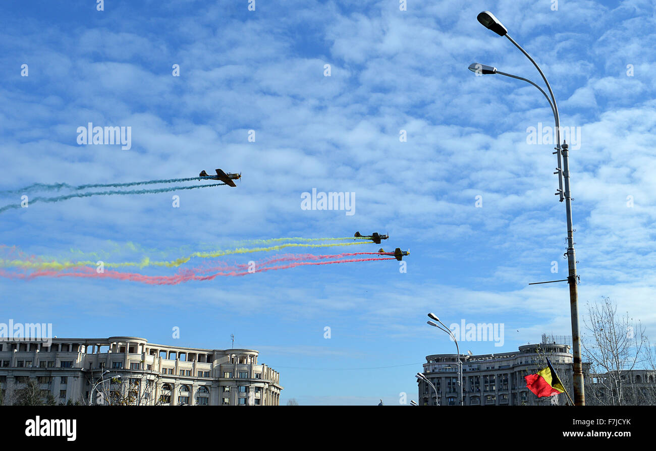 Bucharest, Romania. 1st December, 2015. Aeroplanes fly down Freedom Boulevard (Bulevardul Libertatii) with smoke - Stock Image