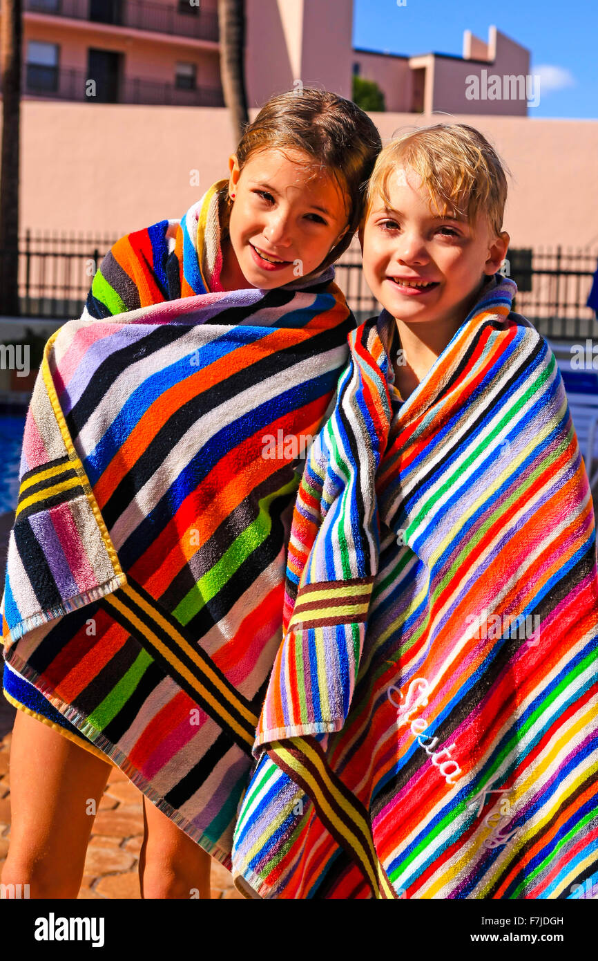 Children wrapped in towels after taking a swim during their summer vacation in Florida - Stock Image