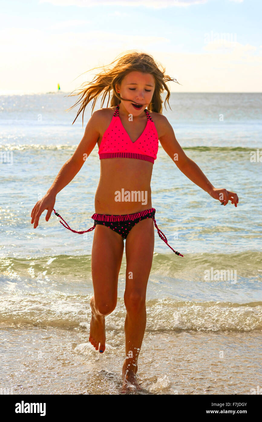 Nine year old female in her bikini walks out of the Gulf of Mexico on a summer's day in Florida - Stock Image