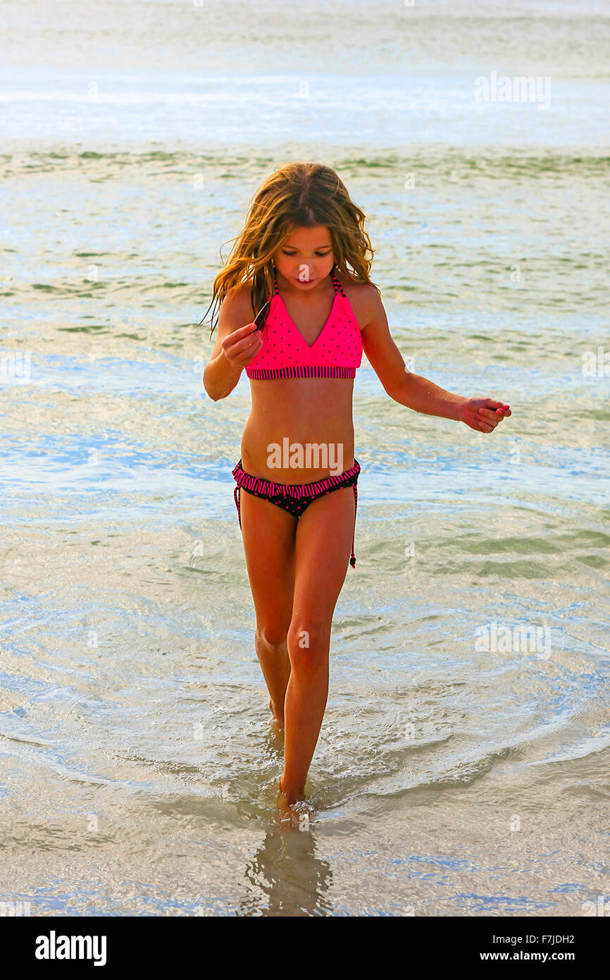 Nine year old female in her bikini seeks out sea shells from the Gulf of Mexico on a summer's day in Florida - Stock Image